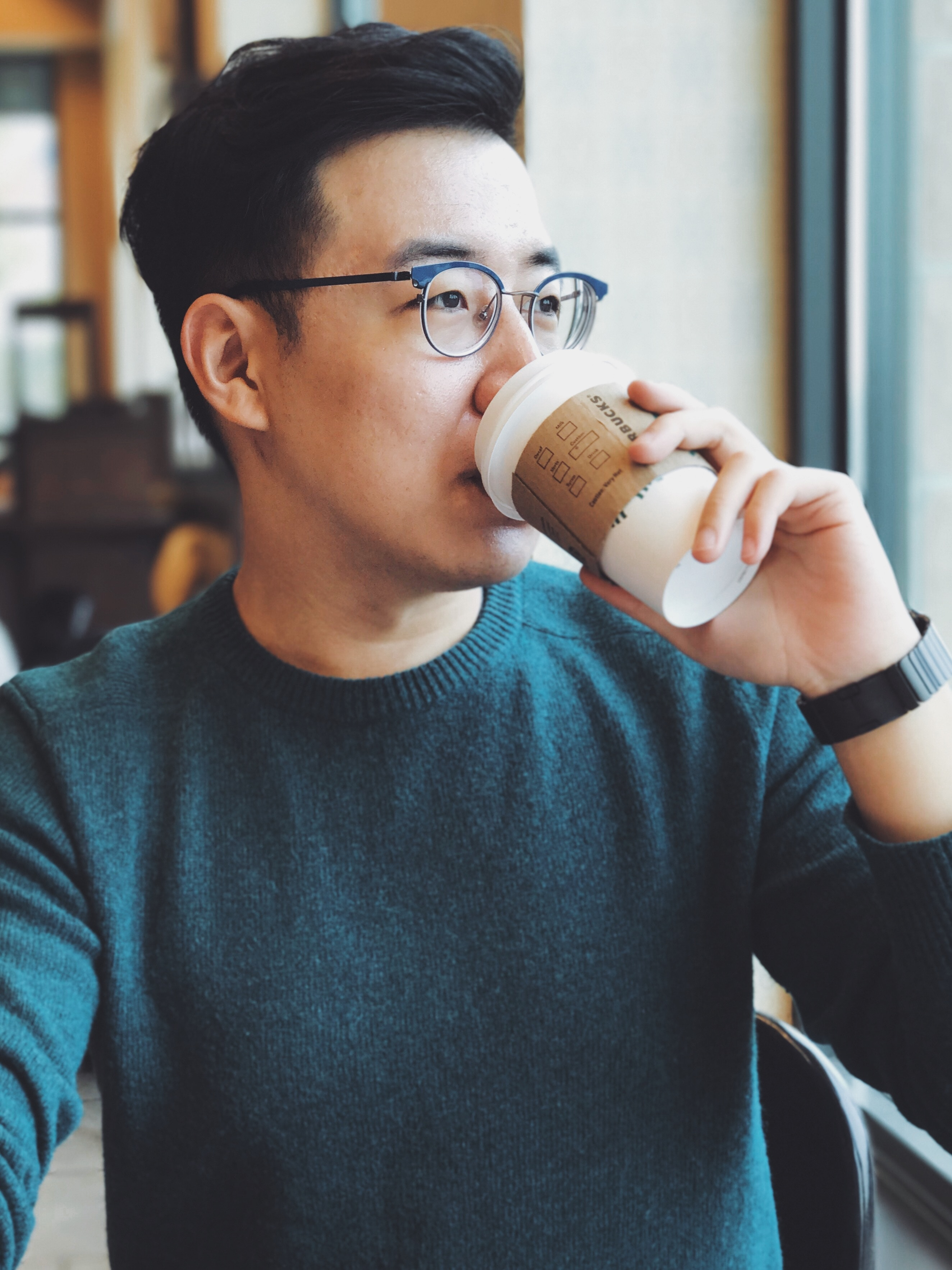 an asian man drinking coffee as he land jobs in Singapore in 2018